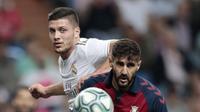 Penyerang Real Madrid, Luka Jovic berebut bola dengan pemain Osasuna, Raul Navas  pada lanjutan pertandingan La Liga di stadion Santiago Bernabeu, Spanyol (25/9/2019). Real Madrid menang 2-0 atas Osasuna. (AP Photo/Bernat Armangue)