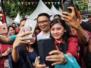 Gubernur Jawa Barat Ridwan Kamil berswafoto bersama warga saat acara Family Day Artha Graha Peduli (AGP) di Pasar Akhir Pekan SCBD, Jakarta, Minggu (25/11). Ridwan Kamil menyempatkan berolahraga sebelum bertolak ke Bandung. (Liputan6.com/Fery Pradolo)