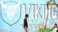 Seorang warga melintas dekat mural Viking di Bandung. (Bola.com/Nicklas Hanoatubun)