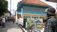 Pelukis di Palembang menggambarkan suasana Kampung Arab Al-Munawar Palembang dikertas kanvas (Liputan6.com/Nefri Inge)
