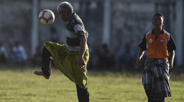 Seorang pria mengenakan sarung berusaha mengontrol bola saat merayakan HUT ke-74 RI di Blang Pidie provinsi Aceh (17/8/2019). Indonesia merayakan kemerdekaan yang ke-74 dari pemerintahan kolonial Belanda. (AFP Photo/Chaideer Mahyuddin)