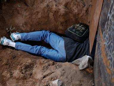 Seorang imigran Honduras merangkak melalui lubang di bawah pagar perbatasan AS di Playas de Tijuana, Meksiko, Selasa (4/12). Banyak imigran yang memilih untuk menyeberangi dinding perbatasan AS. (AP Photo/Rebecca Blackwell)