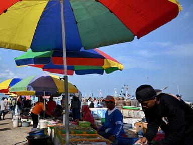 Pedagang menunggu pembeli di pasar ikan di Kedonganan, Denpasar, Bali (17/10/2019). Pasar Ikan Kedonganan merupakan salah satu pasar tradisional yang menjual berbagai jenis hasil tangkapan laut yang masih segar. (AFP Photo/Sonny Tumbelaka)