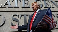 Aktor Hong Kong, Howard berekspresi sebagai Presiden AS Donald Trump, Hong Kong, Rabu (25/1). Aksi tersebut sebagai bentuk pengharapan agar hubungan AS dan Korut bisa berjalan dengan baik. (AFP PHOTO / Anthony WALLACE)