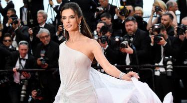 """Model Alessandra Ambrosio berpose saat tiba menghadiri pemutaran film """"The Dead Don't Die"""" selama Festival Film Cannes ke-72 di Prancis (14/5/2019). Model cantik asal Brasil ini tampil memesona dengan gaun putih sutra transparan Ralph & Russo. (AFP Photo/Christophe Simon)"""