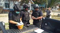Tim Jibom dan Gegana Polda Jateng mengecek benda diduga granat yang ditemukan seorang petani di Puring, Kebumen. (Liputan6.com/Dok. Polres Kebumen untuk Muhamad Ridlo)