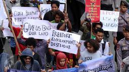 Massa yang tergabung dalam Aliansi Mahasiswa Papua dan FRI-West Papua membentangkan tulisan saat berunjuk rasa di depan kantor PT Freeport di Jakarta, Jumat (7/4). Mereka menuntut penutupan PT Freeport. (Liputan6.com/Helmi Fithriansyah)