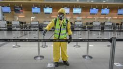 Seorang pekerja mendisinfeksi area check-in dalam Bandara Internasional El Dorado di Bogota, Kolombia, Senin (31/8/2020). Presiden Kolombia Ivan Duque mengizinkan lebih banyak penerbangan domestik mulai September. (Juan BARRETO/AFP)