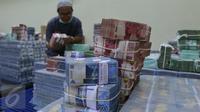 Petugas tengah mengepakan mata uang rupiah di kantor Cash BNI, Jakarta, (17/6). Lebih dari 16.200 ATM yang telah disiapkan untuk melayani kebutuhan transaksi para nasabah BNI maupun nasabah bank lain di seluruh Indonesia. (Liputan6.com/ Angga Yuniar)