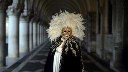 """Seorang peserta bertopeng emas dan kostum tradisional berdiri di St Mark Square selama Karnaval Venesia di Italia, Sabtu (28/1). Karnaval ini bertema """"Creatum: Civitas Ludens"""". (FILIPPO MONTEFORTE/AFP)"""