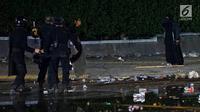 Aparat kepolisian dari Satuan Brimob berusaha menahan perempuan bercadar hitam dengan kabel menjuntai di tangan berusaha mendekat Gedung Bawaslu, Jakarta, Rabu (22/5/2019). Perempuan misterius yang berjalan sendiri tanpa massa ini mengenakan baju gamis warna hitam. (Liputan6.com/Immanuel Antonius)