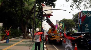 Petugas Suku Dinas PE Jakarta Pusat bersama Satgas PJU, mencabut dan menggeser tiang listrik dan lampu penerangan jalan yang menghalangi jalur sepeda di trotoar Jalan Asia Afrika dan Jalan Gelora, Senayan, Jakarta, Rabu (1/8). (Liputan6.com/Johan Tallo)