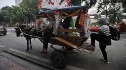 Warga menaiki delman di kawasan Monas, Jakarta, Selasa (3/7). Larangan beroperasi bagi delman di Jakarta Pusat saat Asian Games diberlakukan untuk mengantisipasi penularan virus oleh kuda. (Merdeka.com/Iqbal Nugroho)