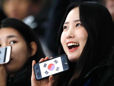 Dua wanita Fans Skating memperlihatkan ponsel mereka yang bergambar bendera Korea Selatan sebelum pertandingan balapan speed skater 1.500 meter pada Olimpiade Musim Dingin 2018 di Gangneung Oval, Korea Selatan, Selasa, (13/2). (AP Photo / Vadim Ghirda)