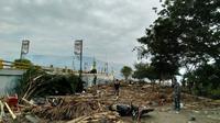 Warga memeriksa kerusakan akibat gempa dan tsunami di Palu, Sulawesi Tengah , Sabtu (29/9). Gelombang tsunami setinggi 1,5 meter yang menerjang Palu terjadi setelah gempa bumi mengguncang Palu dan Donggala. (AFP /OLA GONDRONK)