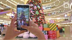 Pengunjung memfoto dekorasi Pohon Natal di Senayan City, Jakarta, Senin (21/12/2020). Senayan City menghadirkan Classic Christmas tree setinggi 18 meter yang dipenuhi dengan hiasan ornamen khas Natal manusia salju serta candy cane. (Liputan6.com/Herman Zakharia)