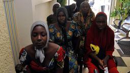 Gadis-gadis sekolah Chibok yang baru saja dibebaskan dari penahanan Boko Haram menunggu untuk bertemu Presiden Muhammadu Buhari di Abuja, Nigeria (7/5). Sebanyak 82 dari 276 siswa perempuan Chibok berhasil dibebaskan. (AP Photo/Olamikan Gbemiga)