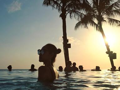 Pada salah satu postingan foto di akun Instagram pribadinya, Bunga Citra Lestari terlihat berpose saat berendam di kolam renang. Foto siluet ini tampak begitu indah. (Foto: instagram.com/bclsinclair)