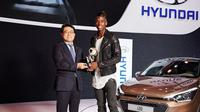 Pogba diminta menjadi model untuk berfoto dengan Hyundai i20 bersama dengan piala yang ia raih.