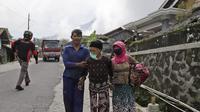 Lansia berjalan mobil bak terbuka yang menunggu saat dievakuasi dari rumah mereka di lereng Gunung Merapi, di Krinjing, Jawa Tengah, Jumat (6/11/2020). Evakuasi dilakukan bagi warga lereng Merapi menyusul peningkatan status aktivitas vulkanik gunung tersebut. (AP Photo/Taufiq Rozzaq)