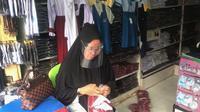 Seorang penjual seragam sekolah di pasar Bambaru, Palu Barat. Aktifitas penjualan di pasar tersebut masih lesu meski menjelang tahun ajaran baru akibat pandemi Covid-19, Kamis (9/7/2020). (Foto: Liputan6.com/ Heri Susanto).