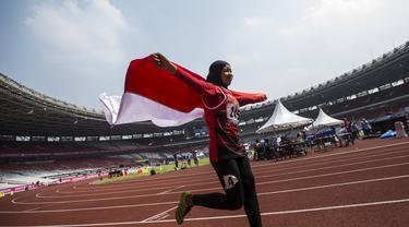 Pelari Indonesia, Tiarani Karisma, melakukan selebrasi usai meraih medali emas Asian Para Games cabang atletik nomor lari 100 meter T42 / T63 di SUGBK, Jakarta, Rabu (10/10/2018). (Bola.com/Vitalis Yogi Trisna)
