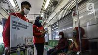 Petugas mensosialisasikan protokol kesehatan kepada penumpang di Stasiun Jakarta Kota, Jakarta, Rabu (28/10/2020). Mengantisipasi lonjakan penumpang saat cuti bersama dan Sumpah Pemuda, PT KCI mengajak pengguna KRL bersatu dan bangkit melawan COVID-19 dengan menerapkan 3M. (Liputan6.com/Johan Tallo)