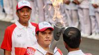Ketua Inasgoc Erick Thohir saat menyalakan api obor Asian Games 2018 ke Presiden Joko Widodo sebelum upacara penurunan Bendera Merah Putih di Istana Negara Jakarta, Jumat (17/8). (Liputan6.com/Pool/Eko)