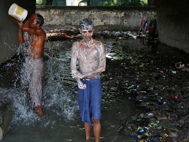 Dua laki-laki mandi di bawah sebuah jembatan di daerah kumuh di Kalkuta, India (26/5/2016). Kalkuta adalah salah satu kota pelabuhan penting di India yang merupakan ibu kota Benggala Barat. (REUTERS/Rupak De Chowdhuri)