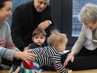 Perdana Menteri Inggris Theresa May bermain dengan bayi saat berkunjung ke pusat kesehatan di London, Inggris, Kamis (22/11). Theresa menjabat sebagai Perdana Menteri Inggris sejak 2016. (Andrew Matthews/Pool via AP)