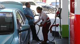Petugas dengan pakaian adat mengisi bahan bakar minyak (BBM) ke sebuah taksi di SPBU, Bali, Rabu (10/10). Petugas SPBU mengenakan pakaian adat Bali untuk menyambut pertemuan tahunan IMF dan Bank Dunia. (Liputan6.com/Angga Yuniar)