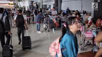 Sejumlah calon penumpang membawa barang mereka menunggu keberangkatan di Bandara Soekarno-Hatta Cengkareng, Banten, Jakarta (9/6). (Liputan6.com/Faizal Fanani)