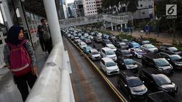 Pejalan kaki melihat kemacetan di Jalan Sudirman-Thamrin, Jakarta, Kamis (20/12). Sejumlah tranportasi multi moda yang sedang dibangun yakni commuter line, MRT, LRT, bus rapid transit (BRT). (Liputan6.com/JohanTallo)