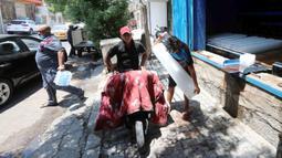 Sejumlah pelanggan membeli balok es dari sebuah pabrik pembuatan es di Baghdad, Irak, pada 5 Juli 2020. Seiring kenaikan suhu yang mendekati 50 derajat Celsius di Baghdad, bisnis pembuatan es di kota tersebut berkembang pesat dengan meningkatnya permintaan balok es. (Xinhua)