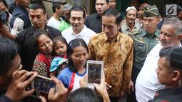 Warga berfoto bersama Presiden Jokowi saat menyaksikan pembagian paket Ramadan di wilayah Penjaringan, Jakarta, Selasa (13/6). Sebanyak 200.000 paket dibagikan gratis untuk meringankan beban masyarakat menjelang Idul Fitri. (Liputan6.com/Angga Yuniar)