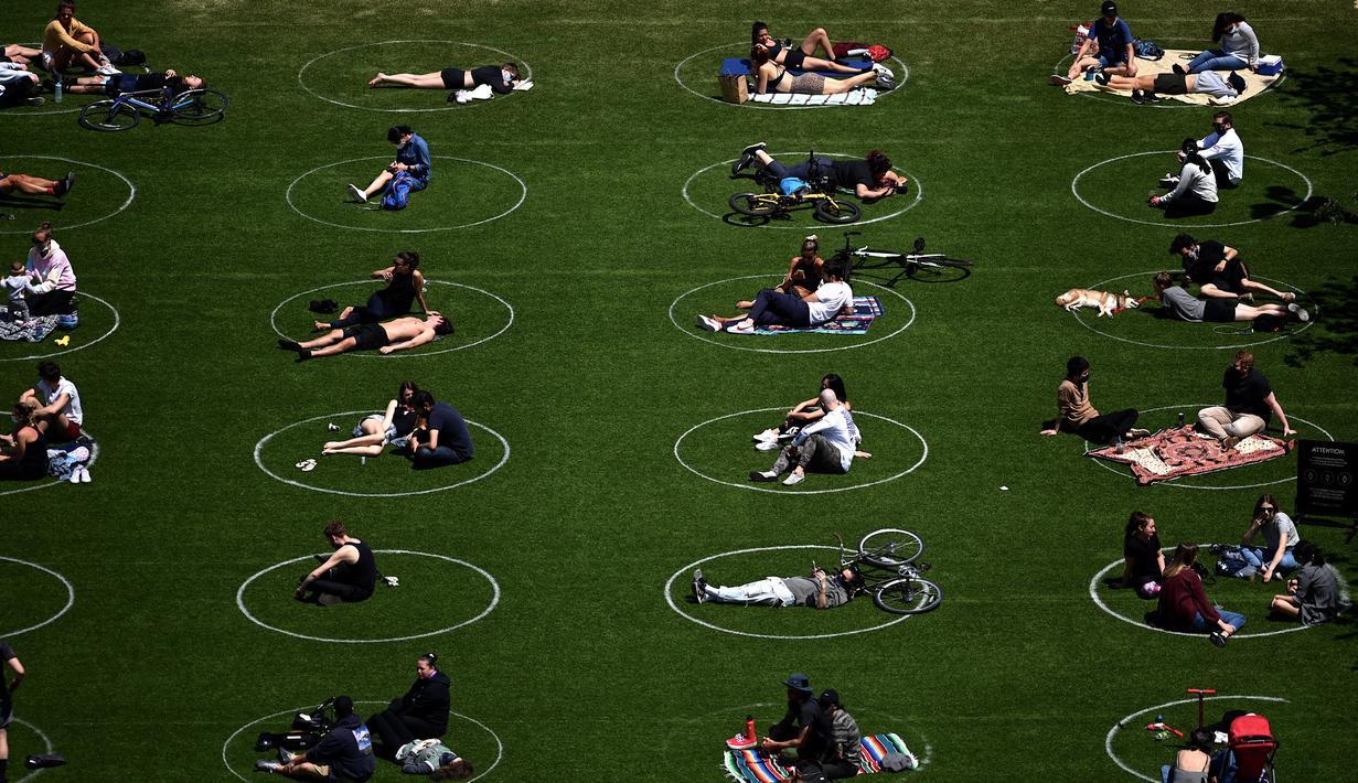 Orang-orang berusaha menjaga jarak dalam lingkaran putih saat bersantai di Domino Park, Brooklyn di Kota New York, Minggu (17/5/2020). Pengunjung taman berjemur dengan tetap menerapkan protokol penularan coorna Covid-19. (Photo by Johannes EISELE / AFP)