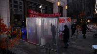 Warga melewati terowongan dengan disinfektan sebagai perlindungan dari Virus Corona COVID-19 di pintu masuk bangunan di Tongzhou, Beijing Timur, Rabu (18/2/2020). Korban meninggal akibat terinfeksi virus corona COVID-19 di seluruh dunia hingga Rabu (19/2) mencapai 2.005 orang. (GREG BAKER/AFP)