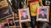 Pedagang membawa bingkai foto Presiden Joko Widodo dan Wakil Presiden terpilih Ma'ruf Amin yang dijualnya di Pasar Baru, Jakarta, Rabu (16/10/2019). Menjelang pelantikan presiden, foto pasangan Jokowi-Ma'ruf Amin mulaih dijual ke pasar umum. (Liputan6.com/Faizal Fanani)