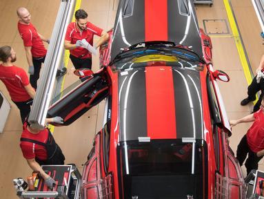 Pekerja memasang pintu mobil sport Porsche GT2RS di pabrik Porsche di Stuttgart, Jerman (26/1). Perusahaan Porsche membagikan bonus besar kepada karyawannya karena hasil penjualan mereka mencapai rekor tertinggi tahun lalu. (AFP Photo/Thomas Kienzle)