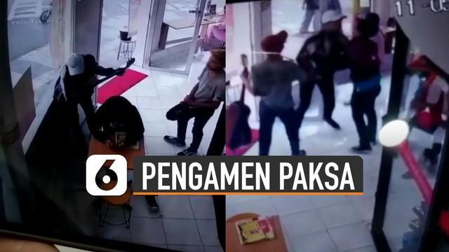 Terekam kamera cctv toko ketika pengamen memaksa pengunjung karena tidak memberikannya uang dan terjadilah keributan.