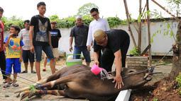 Presenter Eko Patrio saat melihat proses pemotongan hewan kurban di kawasan Cipinang, Jakarta, Jumat (1/9). Eko mempercayakan hewan yang dibeli untuk dikurbankan kepada karyawan-karyawannya. (Liputan6.com/Herman Zakharia)