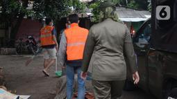 Anggota Satpol PP menghukum warga untuk menyapu jalan saat razia penggunaan masker di Kebon Nanas, Jakarta, Selasa (15/6/2021). Saat kasus positif Covid-19 di Jakarta meningkat, masih banyak warga yang belum menjalankan protokol kesehatan, salah satunya mengenakan masker. (merdeka.com/Imam Buhori)