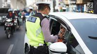 Petugas Kepolisian menindak pengendara mobil berplat nomor genap di persimpangan Jalan Dharmawangsa X dan Jalan Fatmawati, Jakarta, Senin (9/9/2019). Perluasan wilayah ganjil genap berlaku mulai hari ini dan terbagi di beberapa titik, salah satunya Jakarta Selatan. (Liputan6.com/Immanuel Antonius)