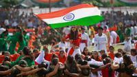 Seorang gadis mengibarkan bendera India saat para siswa melakukan tarian selama perayaan Hari Kemerdekaan India, di Jammu, India, (15/8). India merdeka dari kolonialis Inggris pada tahun 1947. (AP Photo / Channi Anand)