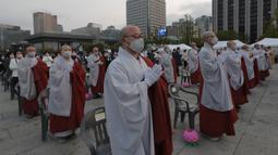 Para biksu mengenakan masker saat merayakan ulang tahun Buddha di Gwanghwamun Plaza, Seoul, Korea Selatan, Kamis (30/4/2020). Ulang tahun Buddha kali ini dirayakan di tengah pandemi virus corona COVID-19. (AP Photo/Ahn Young-joon)