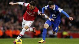 Duel Mesut Oezil dan Bryan Oviedo, Minggu 8 Desember 2013. (AFP/Adrian Dennis)