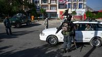 Petugas keamanan menghentikan pengendara mobil saat Hari Raya Idul Fitri di pos pemeriksaan di Kabul, Afghanistan, Minggu (24/5/2020). Taliban mengumumkan gencatan senjata selama tiga hari dengan pemerintah Afghanistan setelah berbulan-bulan bertempur. (WAKIL KOHSAR/AFP)