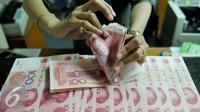 Petugas menghitung uang pecahan 100 Yuan, Jakarta, Kamis (13/8/2015). Biang kerok keterpurukan kurs rupiah dan sejumlah mata uang negara lain adalah kebijakan China yang sengaja melemahkan (devaluasi) mata uang Yuan. (Liputan6.com/Johan Tallo)