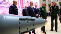 Presiden Vladimir Putin berjalan disamping rudal saat mengunjungi pameran di markas militer Rusia di Moskow (30/1). Kunjungan Putin sebagai bagian dari sebuah konferensi mengenai kampanye Rusia di Suriah. (Mikhail Klimentyev, Sputnik, Kremlin Pool/AP)