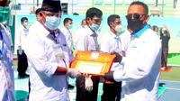 CEO PTPN V Jatmiko K Santosa menyerahkan penghargaan kinerja pemanen terbaik saat perayaan HUT PTPN V ke-25. (Liputan6.com/M Syukur)
